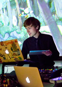 A photo of DJ Daniel C418 Rosenfeld performing in front of a screen ad holding multiple tablets and macbooks.A photo of DJ Daniel C418 Rosenfeld performing in front of a screen ad holding multiple tablets and macbooks. He is youthful and smiling at one of the macbooks