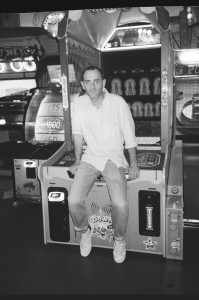 A black and white still of a man resting on an arcade cabinet.