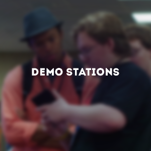 "Two men looking very closely at a device in one of their hands. The text above the blurry photo reads ""Demo Stations"""