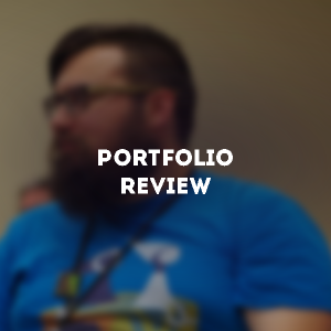 "A bearded man, blurred for effect, looks off to the left of the screen. Above the blurred image is the text ""Portfolio Review"""