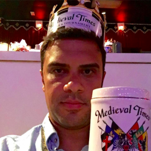 "A picture of Nigel Lowrie. He is wearing a paper crown and holding up a large tankard, both of which are labeled ""medieval times."""