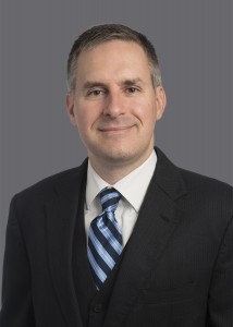 Brian Chellgren, a white man with graying hair at his temples and a blue striped tie leading into his suit.