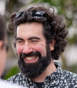 Jake, a smiling man with curly brown hair and a beard, sunglasses perched on his head.