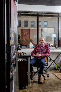 Wes, a bald man with an impressive moustache and a red and blue check shirt, sits in a crowded office overlooking an urban environment.