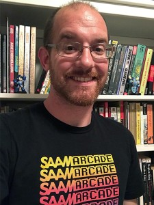 A white smiling man with a beard, standing in front of a bookshelf and wearing a shirt with the text SAAM Arcade repeating.