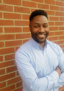 A smiling African American man in a blue buttoned up shirt against a brick wall.