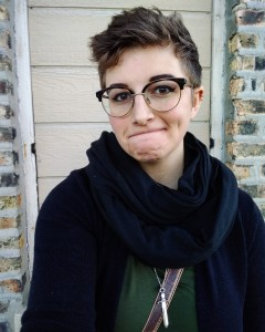 Becca stands with a wry smile, glasses, and a thick scarf.